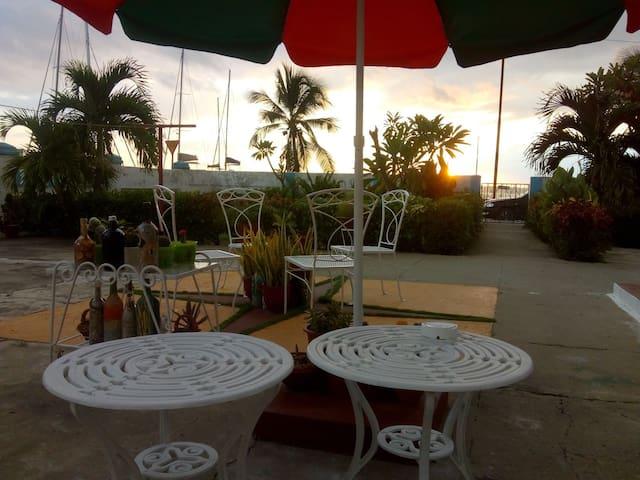 Jardín con sombrillas, sillones, mesa, un espacio para relajarse.