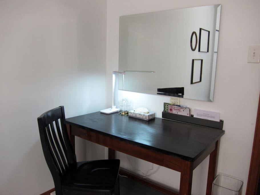 There is a nice size desk with a multi setting lamp and a huge beautiful Art Deco mirror. The desk also has a slide out drawer for laptop use. There are plug converters and USB plugs already to charge your laptop, phone, Kindle, or ipad.