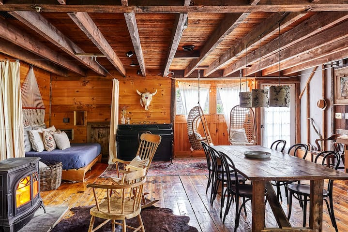 First Floor hangout  // Wood burning stove, queen day bed, hanging chairs, full bathroom with rain shower, sound system , kitchen and the old rustic farm table with seating for 6.