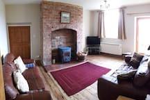 Lounge with log burner, overlooking front garden.