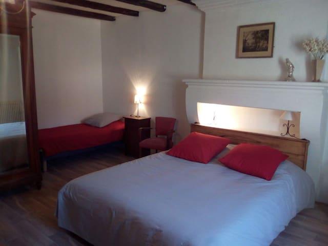 La chambre familiale au rez de chaussée avec un lit double et deux lits simples et une salle de bain.