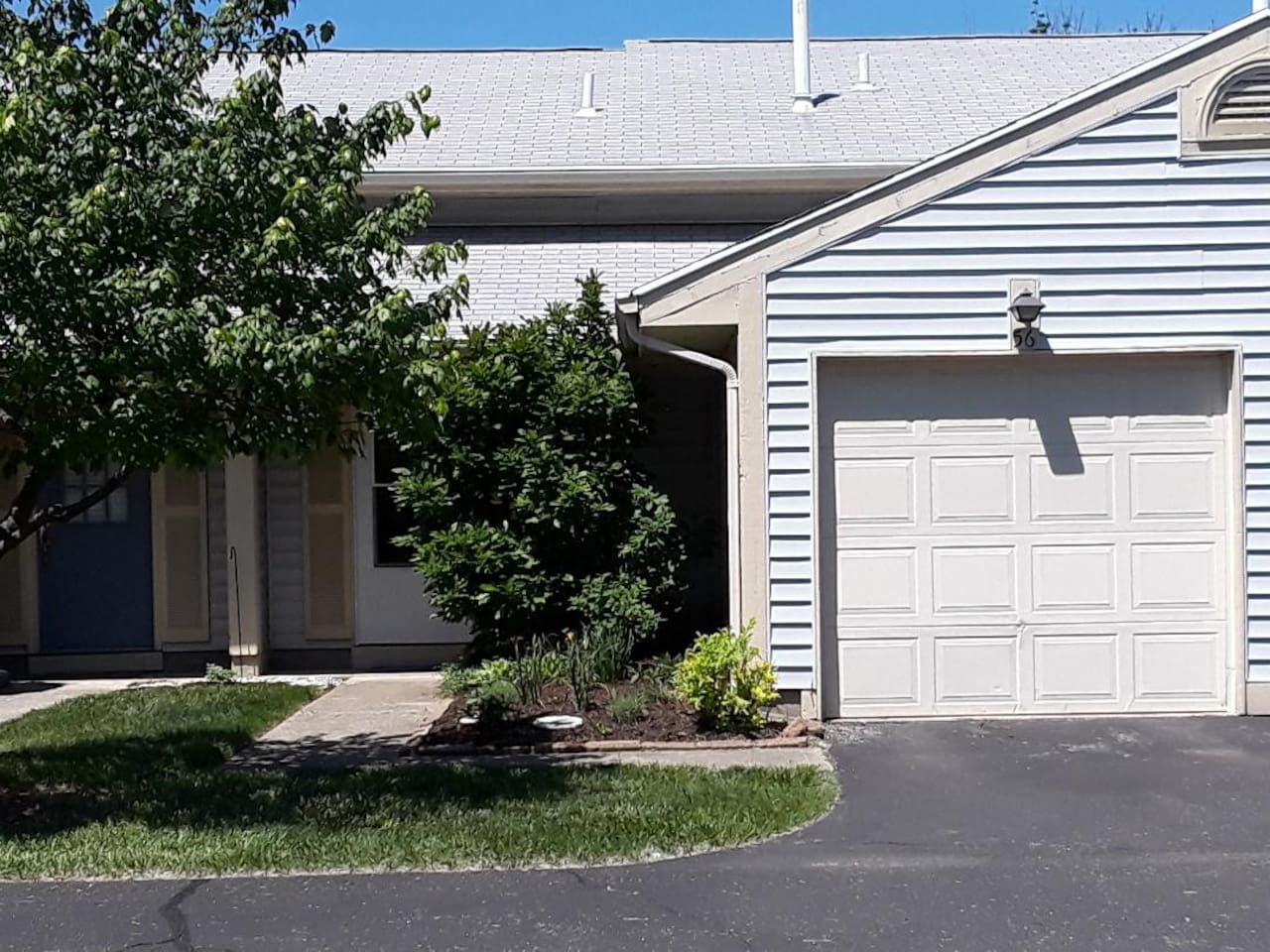 Front of Condo with attached 1 car garage with opener