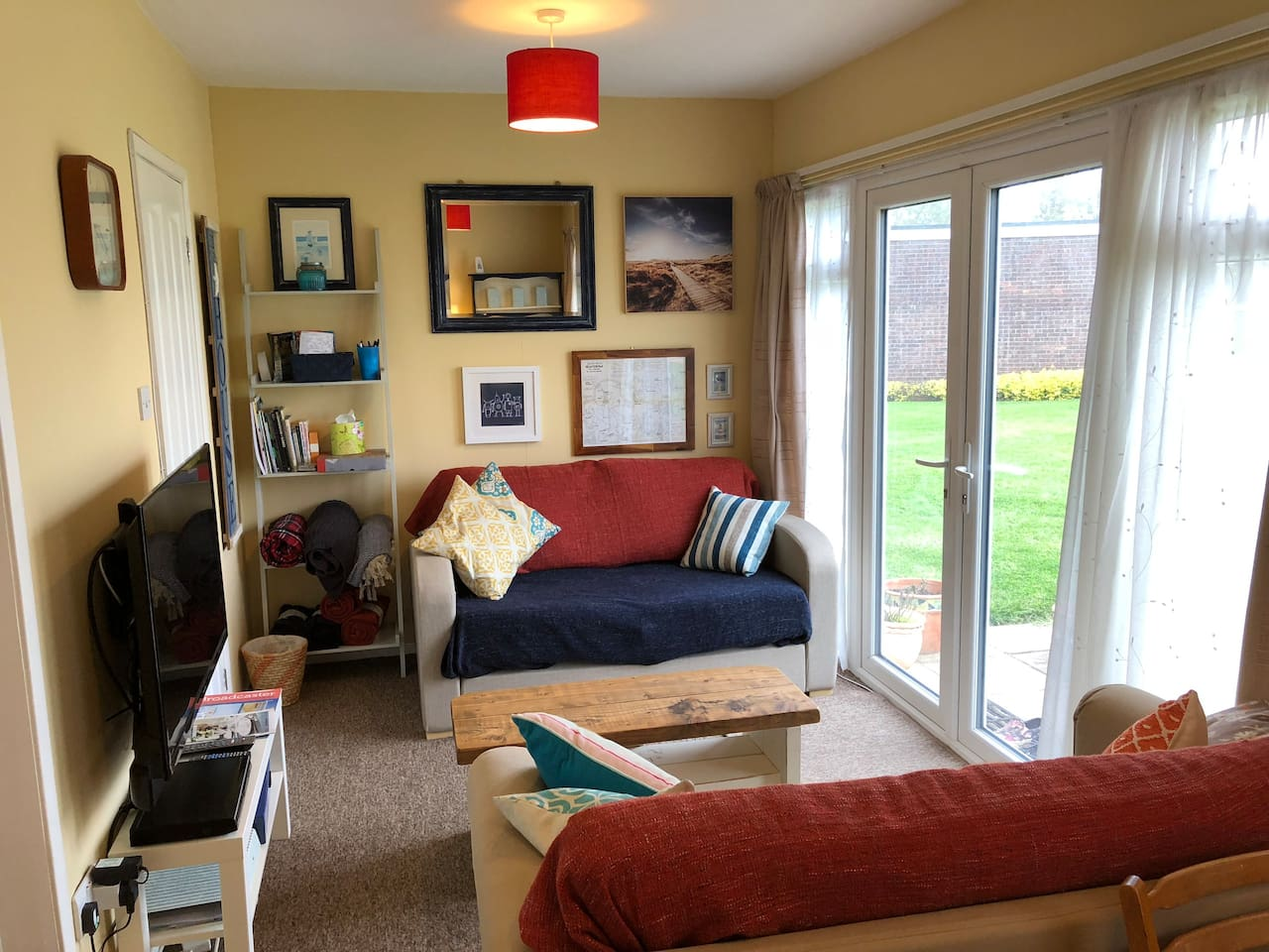 Homely open plan living space with patio doors, TV and DVD player