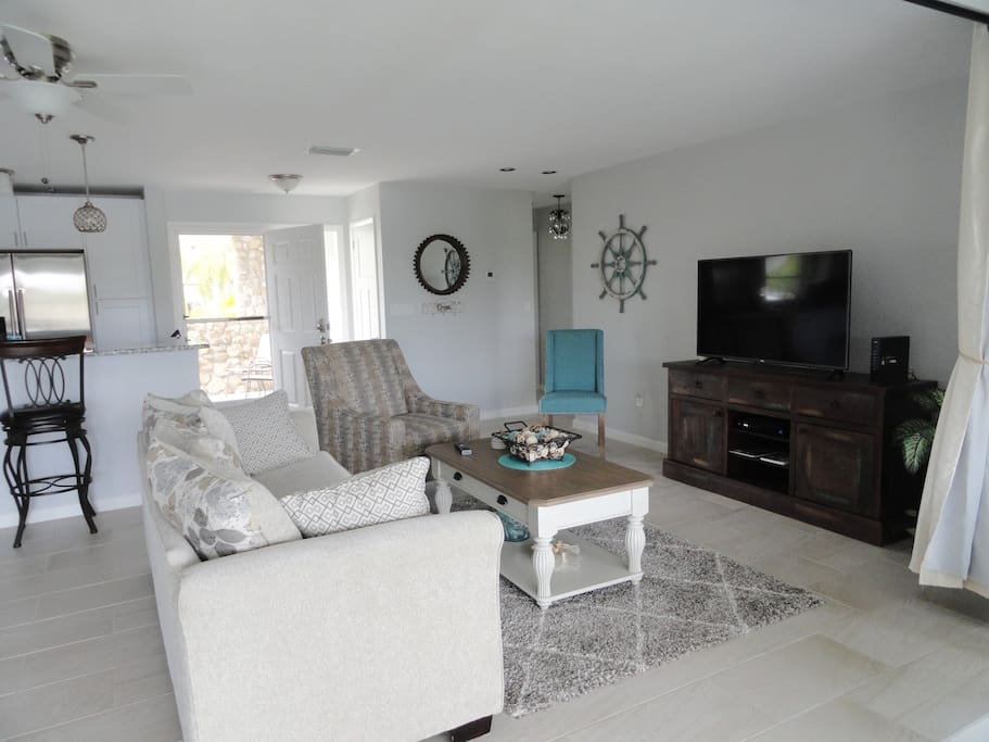 Living area with large flat screen TV and breakfast bar. Glass doors open out onto lanai.