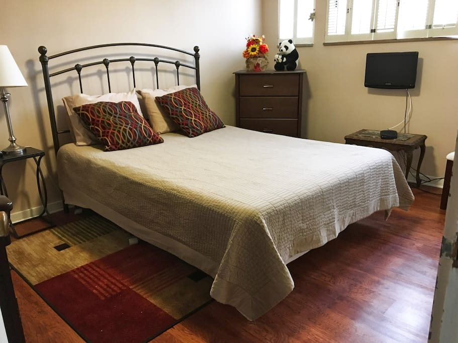 Queen size bed with natural lighting. Bedroom is connected to a  private bathroom.