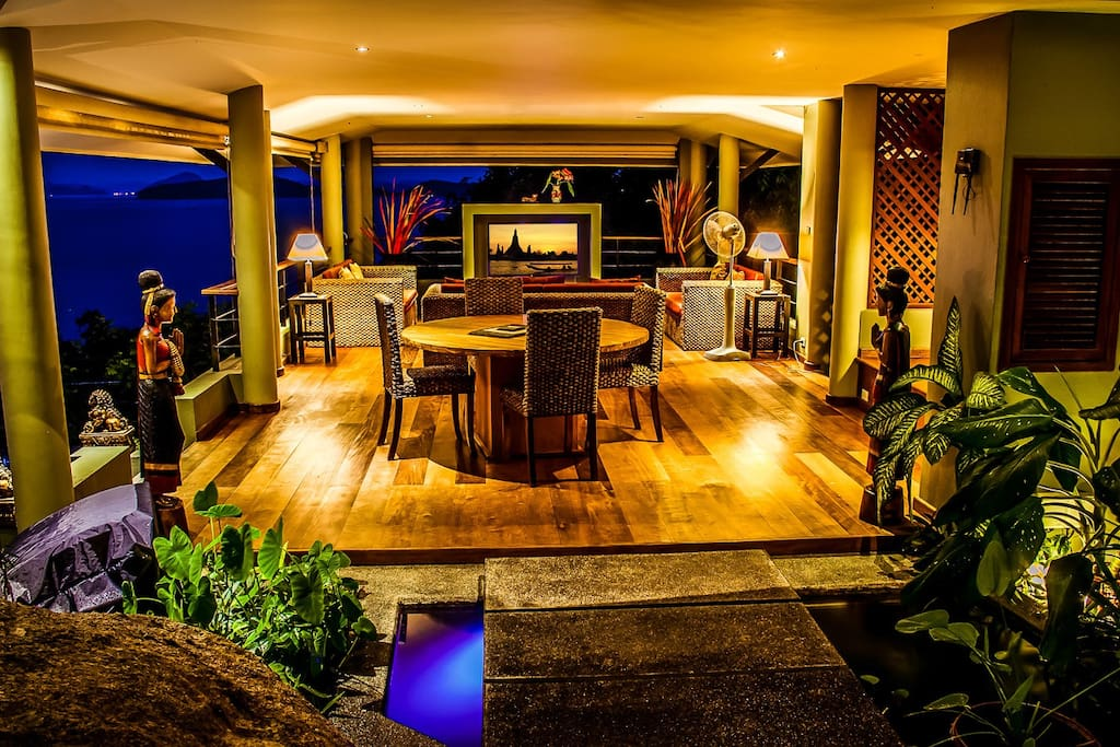 Tropical style Living area romantically lit in the evening time