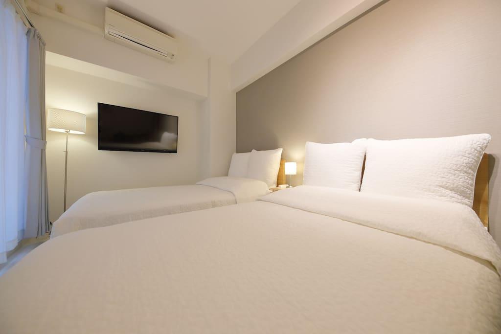 広々ダブルベッド Double bed in spacious room. 宽敞的双人床
