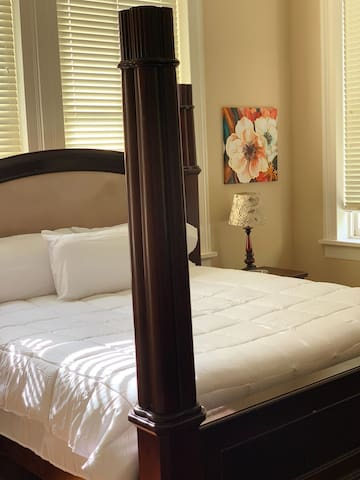 Master bedroom with king size bed and a pull pull out couch is located in the room.