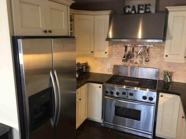 This photo shows a Kitchenaid commercial gas stove and fridge. Cooking great meals will be no problem in this kitchen.