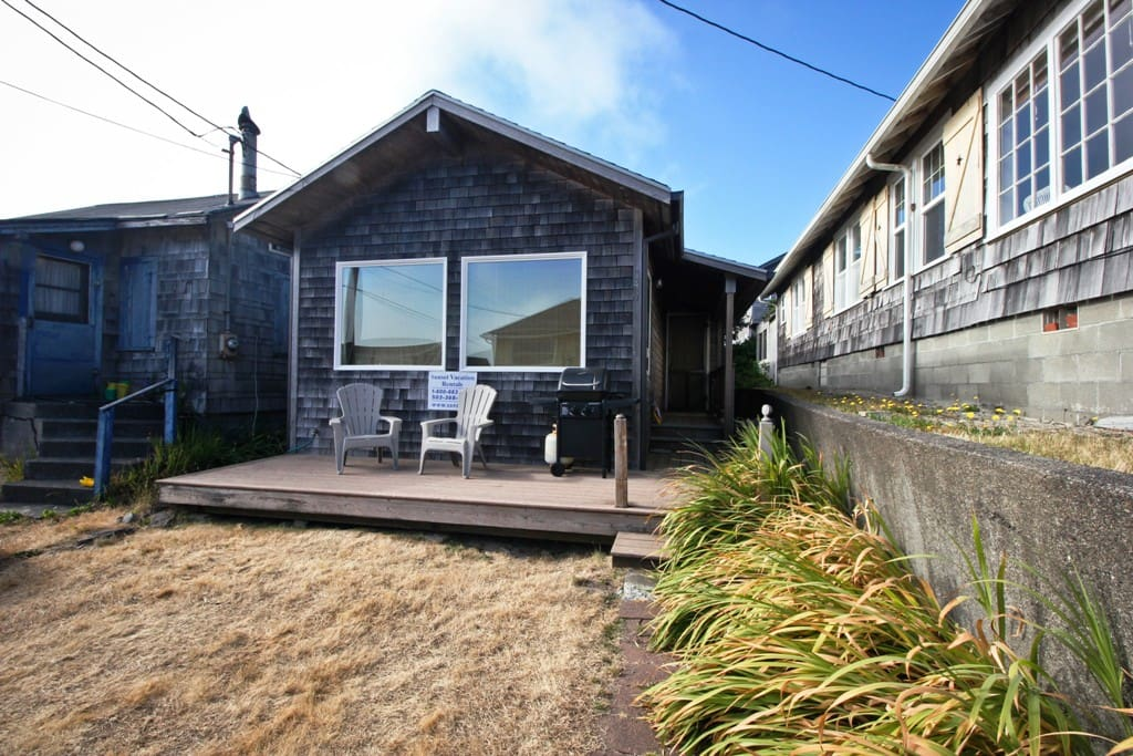 Street view of By the Sea with a small deck with gas BBQ and deck chairs