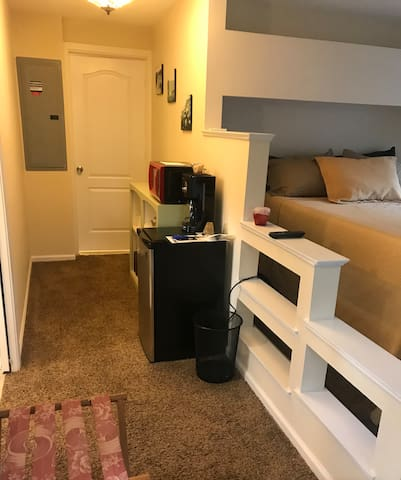 Hallway and lockable door leading to the shared laundry room.  This studio comes with a small refrigerator, microwave, toaster over, coffee machine, plates, cups and silverware.