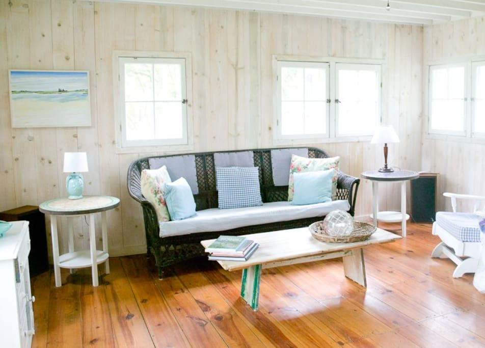Living room with wide plank wood floors and white washed pine walls.