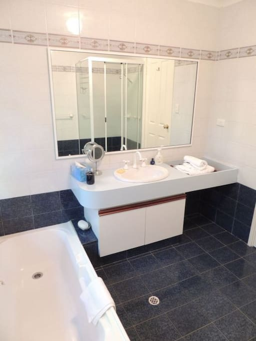 Private ensuite bathroom with toilet, shower and bath