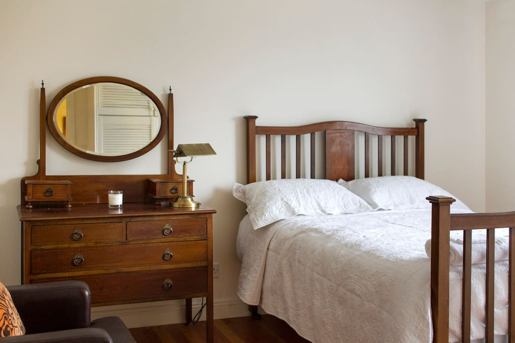 Large bedroom with antique furniture and extra comfy bed.