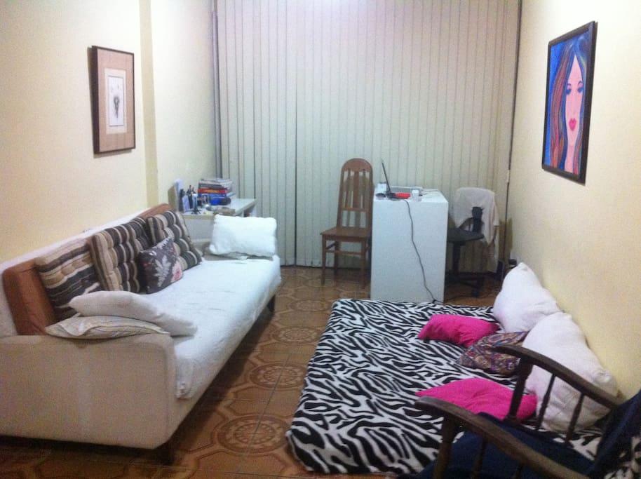sofá cama  de casal na sala e fouton de casal tem ainda dois colchões de solteiro