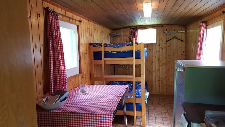Kajüten Bett, Tisch, Schrank, Lavabo und kleiner Kochherd mit Holzfeuerung und kleiner Kühlschrank. So sieht die Ausstattung des Wohnwagens aus.