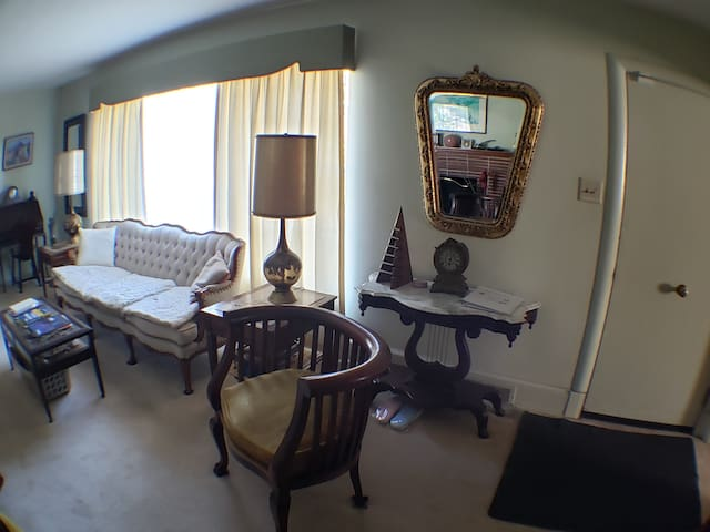 This is the front sitting room. to the left you see the front picture window and to the right you see the inside of the front door. To your right is the office and behind you is the hallway.