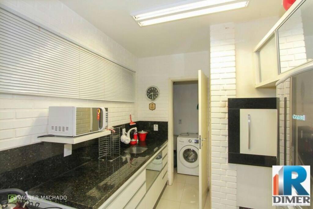 cozinha com churrasqueira e área de serviço