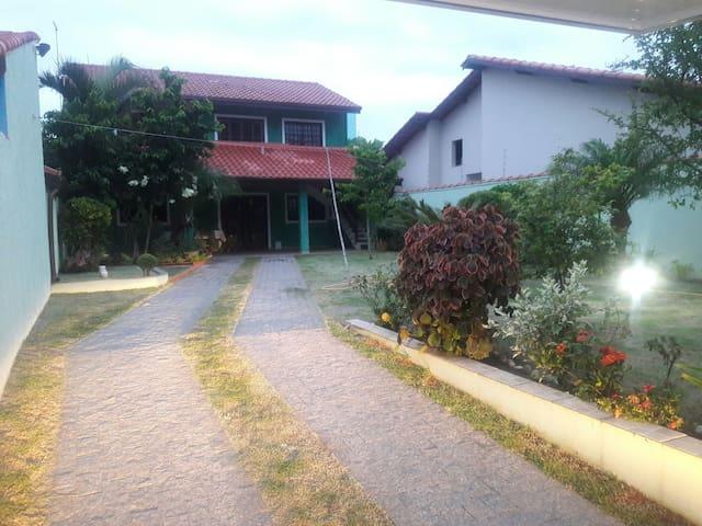 Foto da fachada principal e jardim. Entrada da garagem