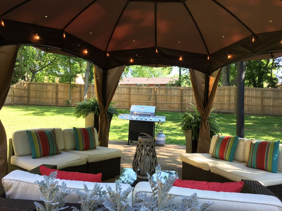 Covered gazebo with gas grill and fire pit in private fenced in yard.