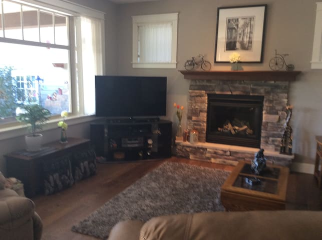 Living room with gas fireplace, couch and two reclining chairs