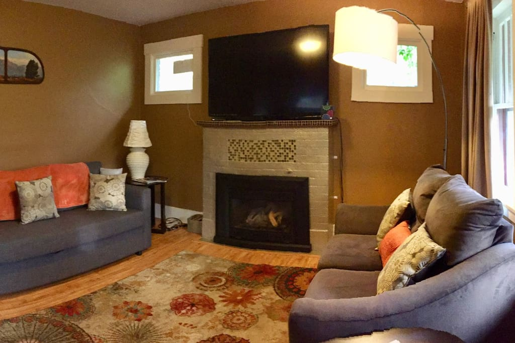 """Living room view from front entrance.  50"""" """"Smart"""" TV with DVD player, a few DVD's & Antenna for local Channels. Fold out couch"""