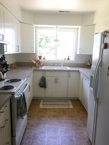 Kitchen with stovetop, oven, dishwasher, microwave, and fridge for guest use.