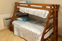 Bunk bed with one full bed and two twin beds.