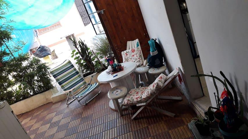 Patio techado, con sillas, ganchos y mesas.