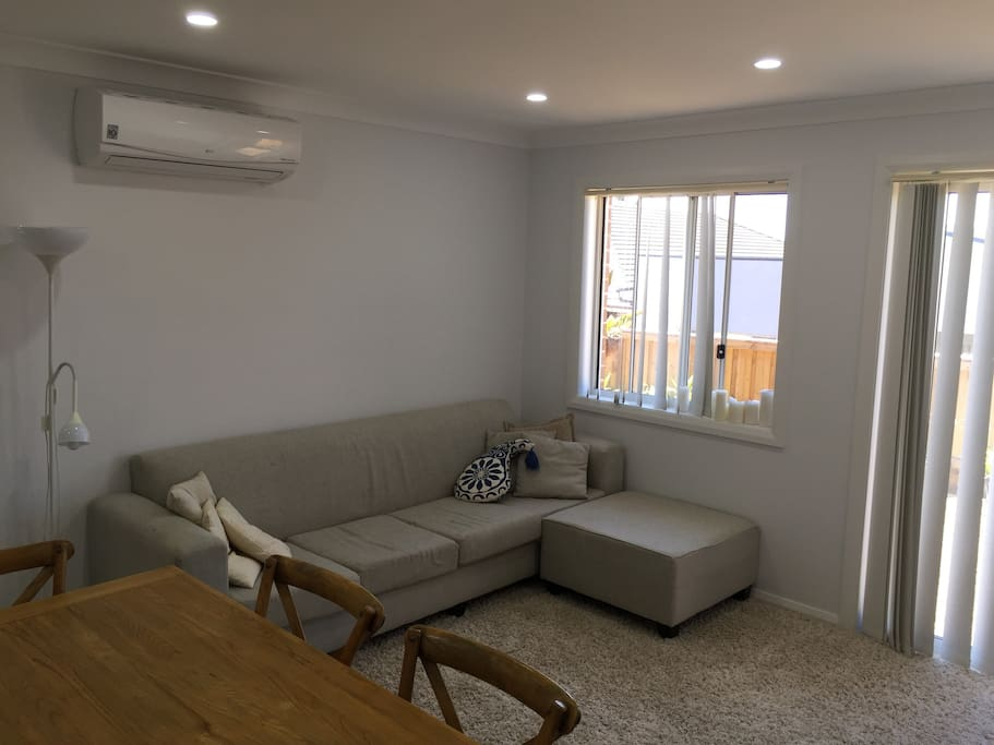 Living area with 4 seater sofa and AC