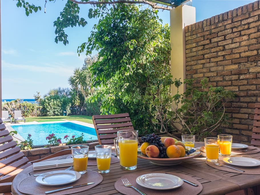 Outdoor dining on your private patio overlooking the garden, pool, and ocean