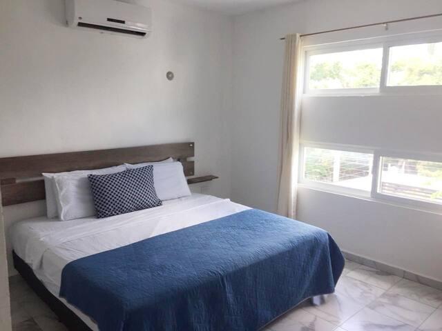 Recámara secundaria tranquila con cama queen size, minisplit, ventilador y hamaquero.