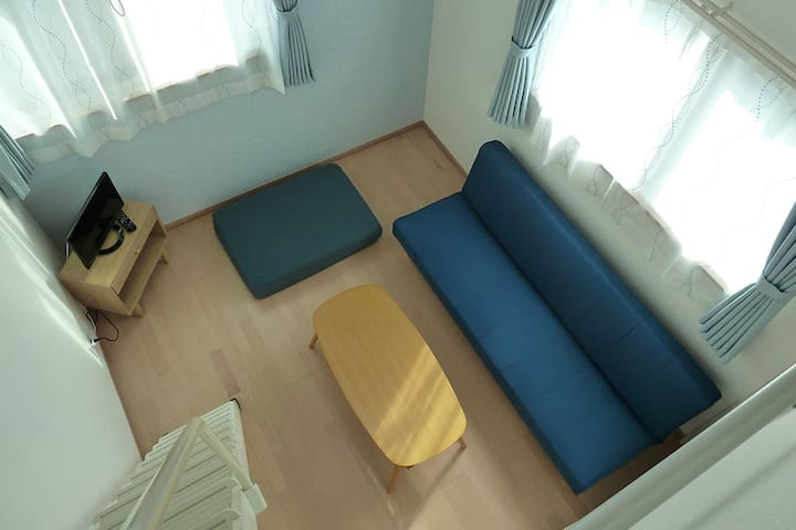 Room 202:Tall ceiling makes the living room feels more open and wide. The sofa is big enough for 3 adults.天井が高く、開放感のあるリビングルーム。ソファは3名がゆったりとくつろげます。