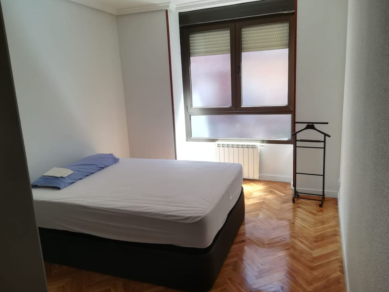 Habitación con cama de matrimonio, colchón viscoelástico, canapé, amplio armario empotrado con espejo.