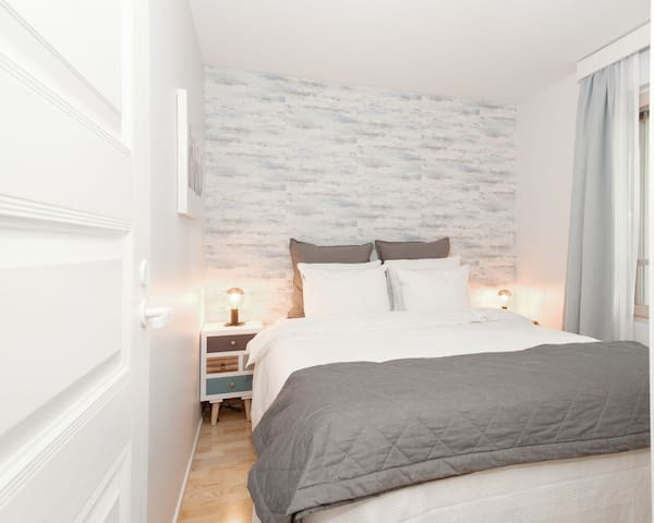 The second bedroom offers a comfortable queen bed with two side tables and reading lamps