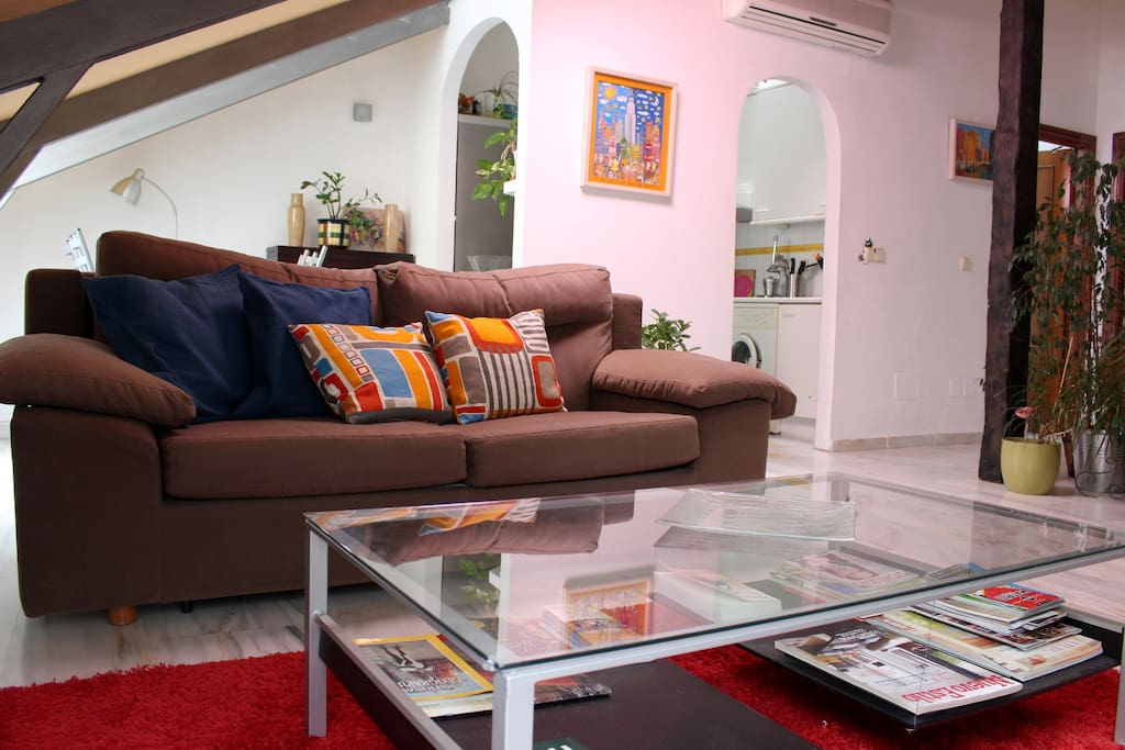 Living room. A comfy couch, TV and an aire area available for our guests.