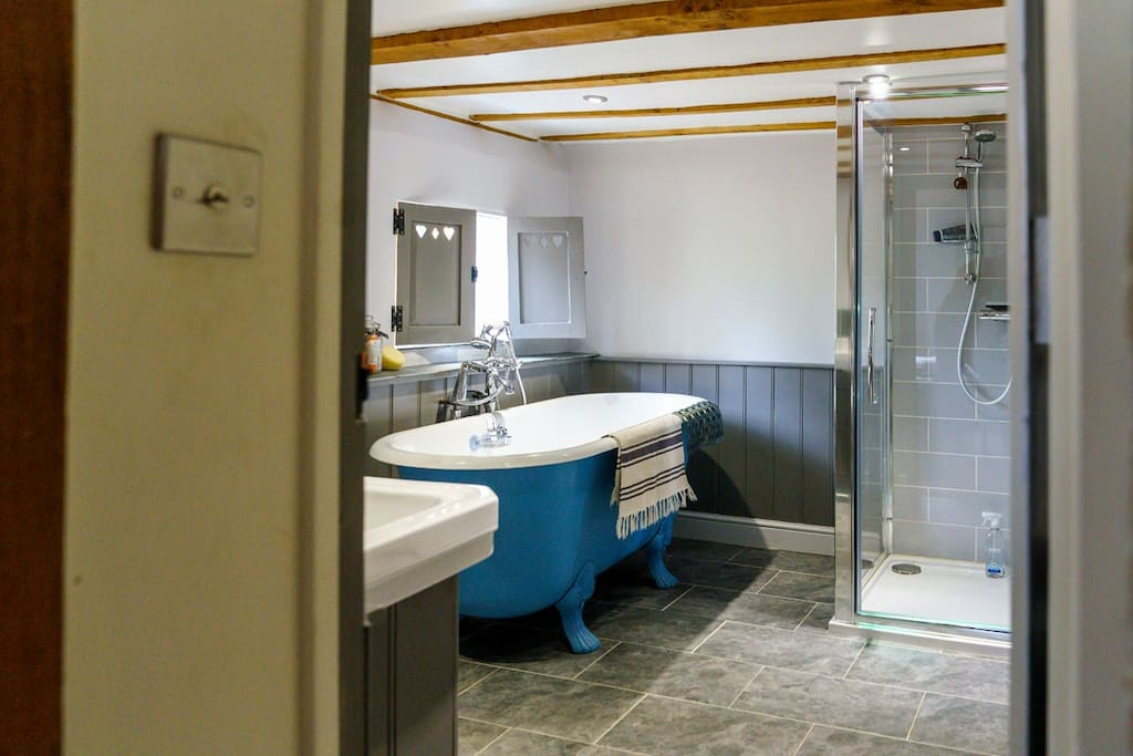 En suite bathroom with separate roll top bath and shower.