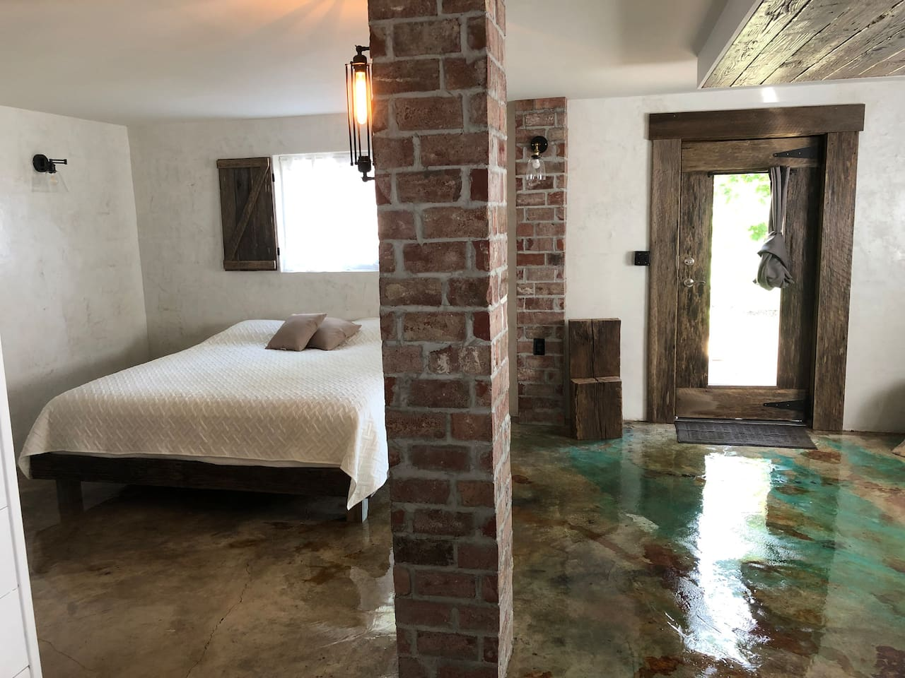 A king size bed sits amid the reclaimed brick columns and the burnished stucco walls.  The wood for the shutters and the door came from a barn built in 1900.   The wood beam entry table is from a barn built in 1850.  Even the bed frame is reclaimed.