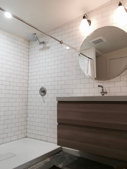 A 3' x 5' spa-like shower is surrounded by subway tile and a floating vanity.