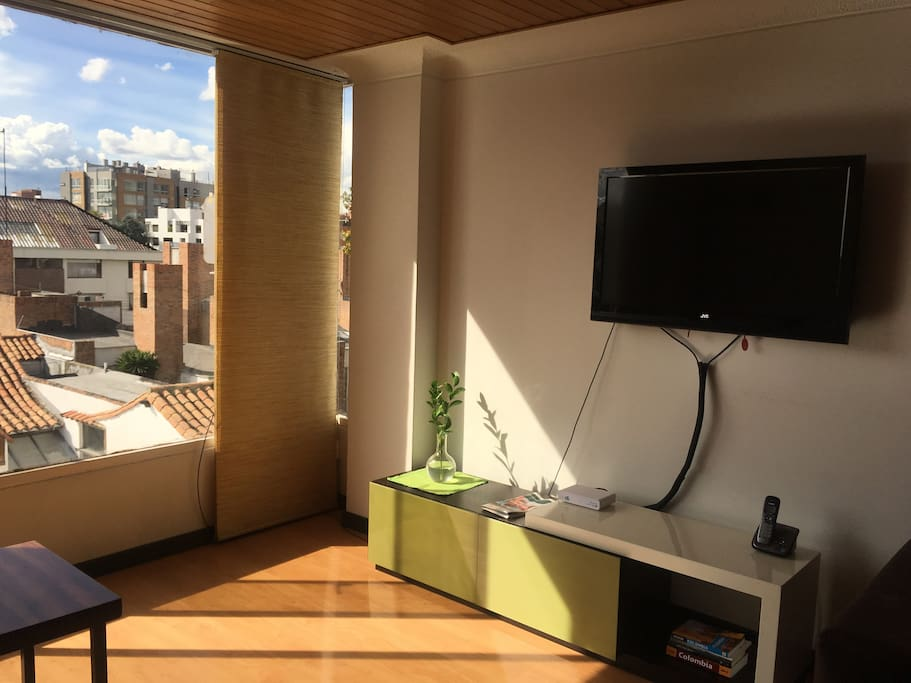 Flat screen TV in living room and wall to wall window with a gorgeous view of the exclusive Santa Barbara neighborhood.