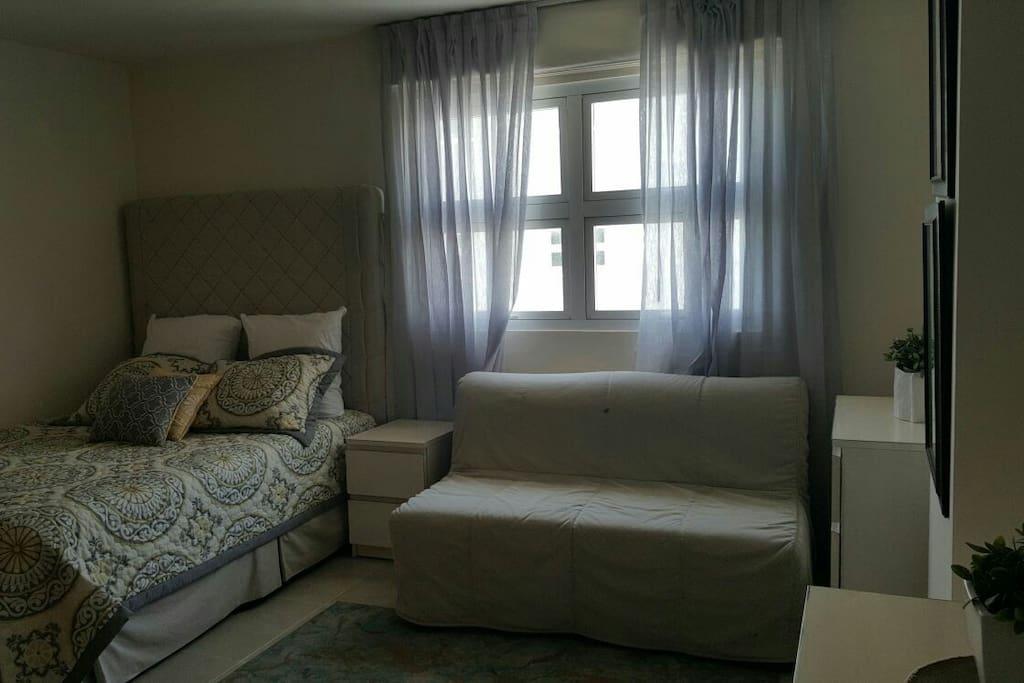 Habitación con cama doble, sofá cama para dos personas, televisor plasma, baño privado, vista lateral al.mar caribe