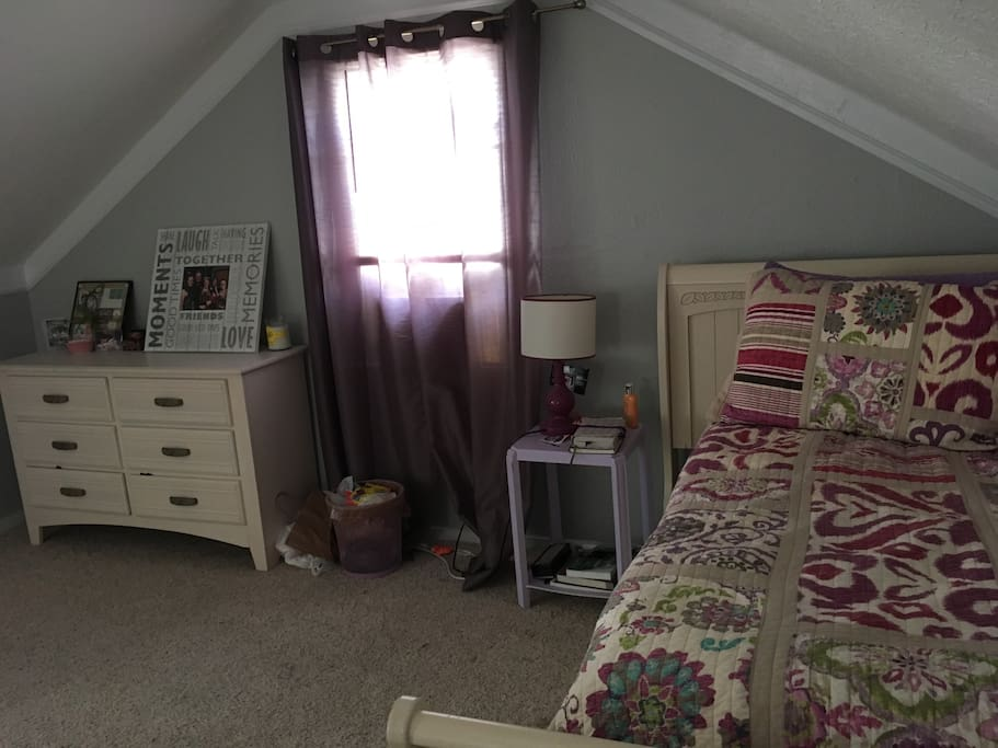Upstairs bedroom with twin bed, and street view.