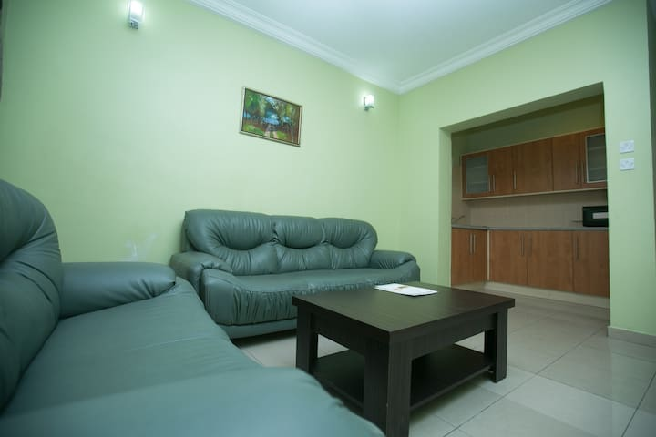 A private living room area, furnished with Air-conditioning, TV, a guest toilet and a small kitchen net area.