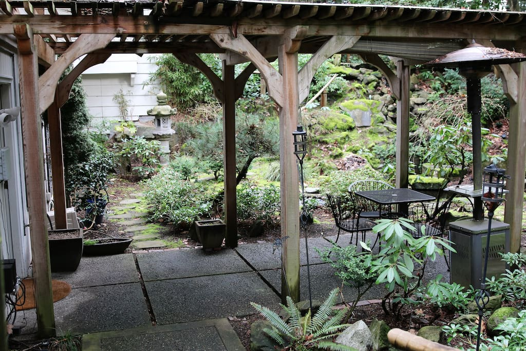 Peaceful covered cedar porch sits next to the koi pond.