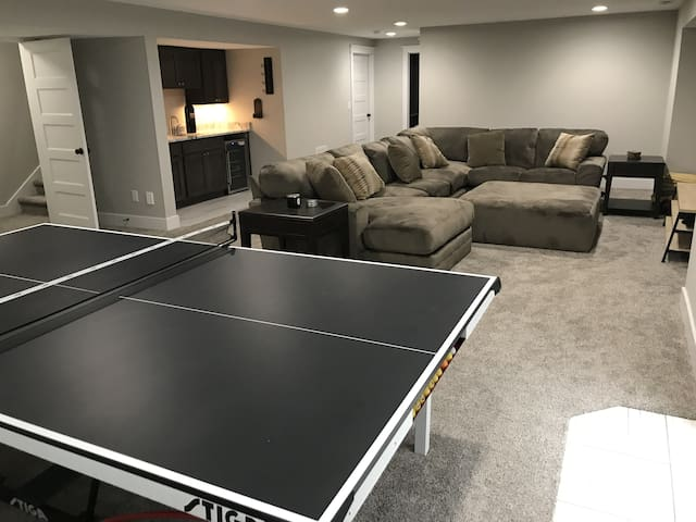 """Basement living room with ping pong table, oversized sectional and ottoman, 65"""" 4K TV, Xbox One, and wet bar"""