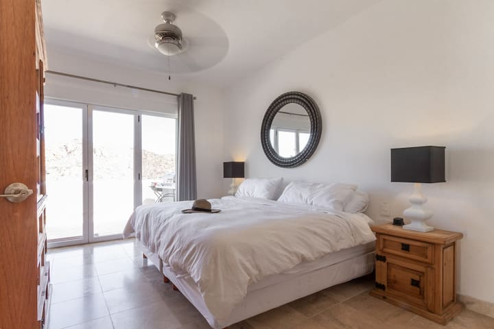 Master bedroom with plenty of storage space, door to the patio, and personal fan
