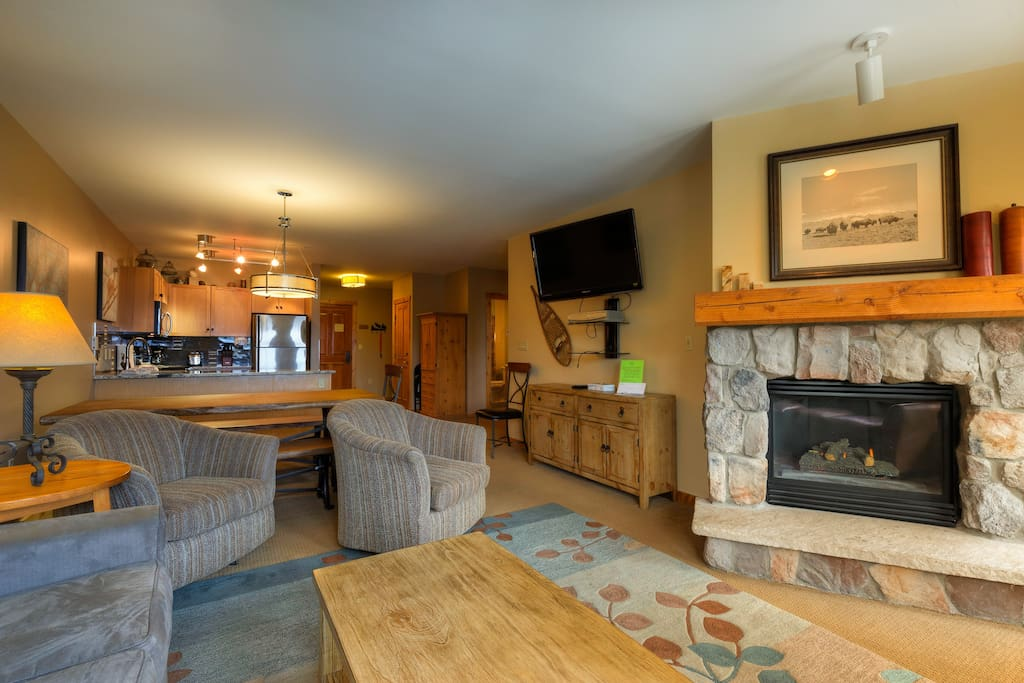 The living area features a mounted flat screen TV next to a beautiful gas fireplace.