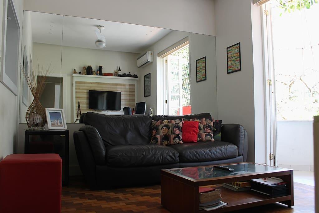 Apartamento completo com sofá, super confortável, adega de vinhos, um espelho grande na parede e uma varanda.
