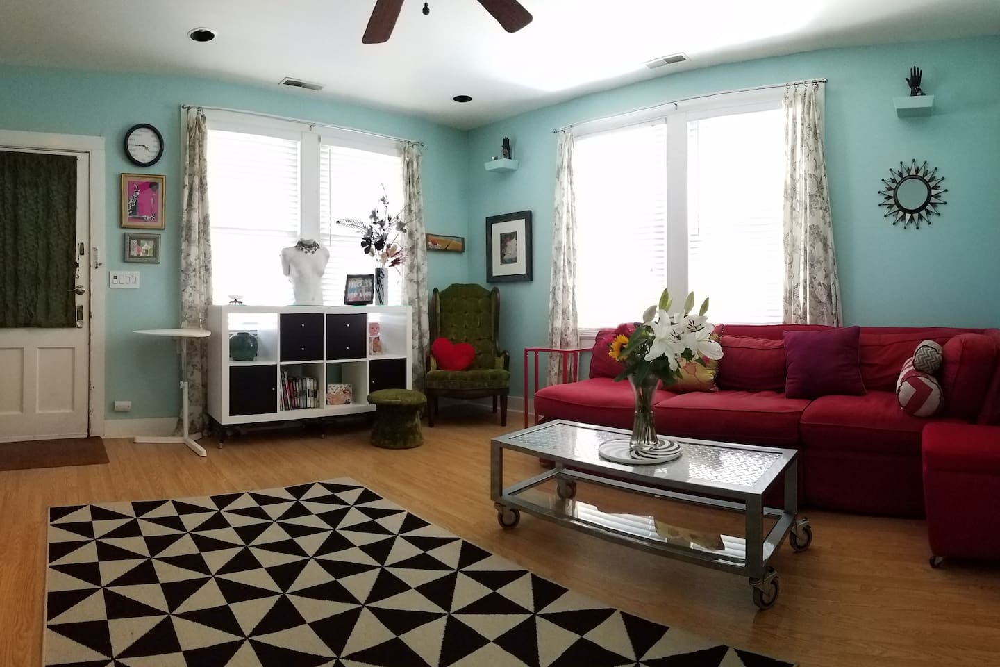 Is this a living room,  or a whimsical art gallery with a sectional couch and personal kitchenette? Enjoy a cup of coffee while perusing some of the eclectic art in this colorful den!