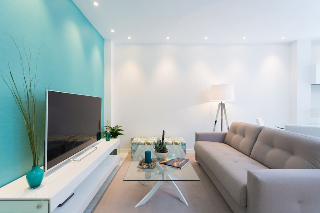 The living room has air conditioning and a comfy sofa (which can turn into a bed) a 55'' TV with Netflix access and a large dining table.